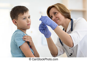 Doctor holds syringe and teenager patient. Little brave boy before injection.