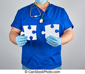 doctor in blue uniform and sterile latex gloves holds white big blank puzzles
