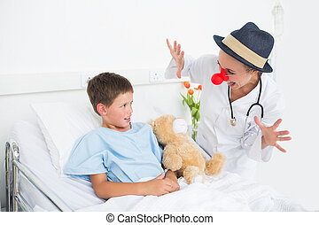 Doctor in clown costume entertaining ill boy in hospital -...