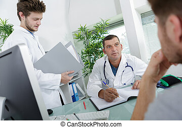 Doctor in consultation with patient, student doctor holding notes