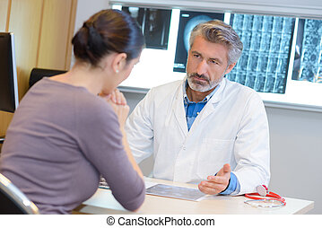 Doctor in consultation with woman, grave expression