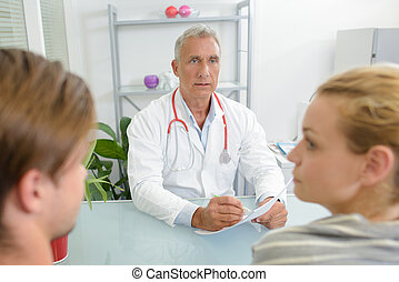 Doctor in consultation with young couple