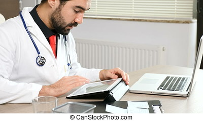 Doctor in his office at the laptop