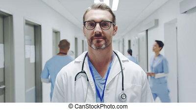 Doctor in hospital corridor smiling to camera 4k