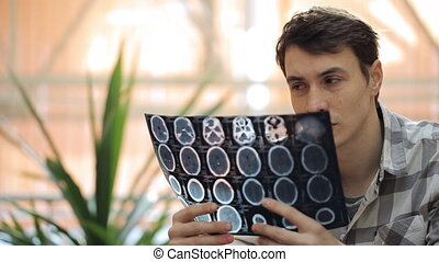 Doctor in informal clothes keeps roentgenogram in his hands and thinks.