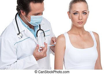 Doctor in mask doing vaccination to young attractive woman. Standing over white background