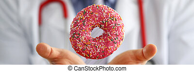 Doctor in office holding in hand pink doughnut close-up. Products that can not be consumed in certain diseases concept
