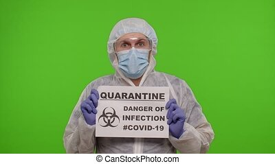 Medical worker doctor in PPE suit showing warning text slogan on paper - Quarantine Danger Of Infection Covid-19. Isolated on chroma key background during coronavirus pandemic lockdown. 4k footage