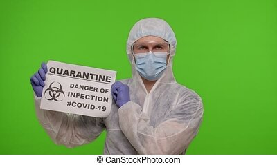 Medical worker doctor in PPE suit showing warning text slogan on paper - Quarantine Danger Of Infection Covid-19. Isolated on chroma key background during coronavirus pandemic lockdown. Slow motion