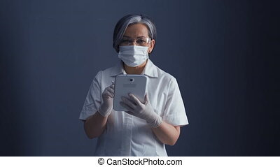 Doctor in protective mask and goglass and gray hair with ...