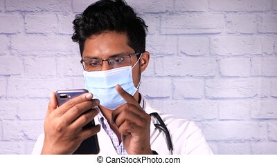 doctor in protective mask using smartphone in the hospital.