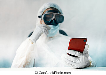 Doctor in the protective suit with smartphone