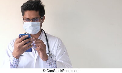doctor in white coat and surgical mask using a smartphone while standing indoor