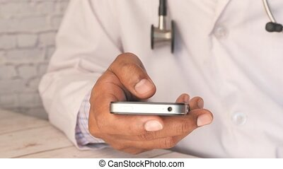 doctor in white coat using a smartphone.