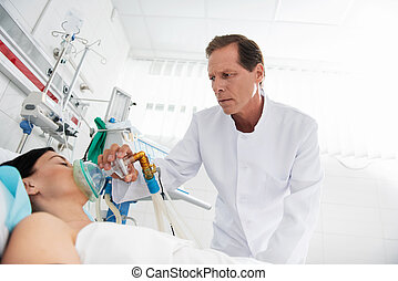 Doctor in white lab coat putting oxygen mask on unconscious young lady