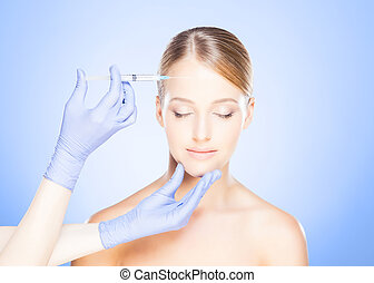 Doctor injecting in a beautiful face of a young woman....