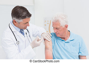 Doctor injecting senior patient in clinic
