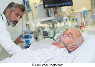 doctor is checking a senior patient with oxygen mask