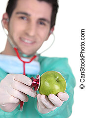 Doctor listening to apple heartbeat with stethoscope