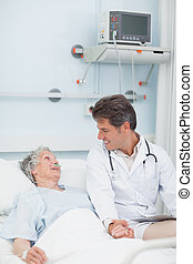 Doctor looking at a patient while taking her hand