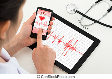 Doctor Looking At App For Health - Close-up Of Doctor...
