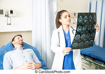 Doctor looking at CT scan results