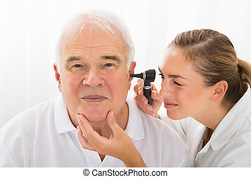 Doctor Looking At Patient's Ear Through Otoscope