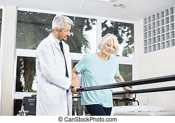 Doctor Looking At Senior Woman Walking Between Parallel Bars