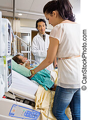 Doctor Looking At Woman Standing By Patient's Bed