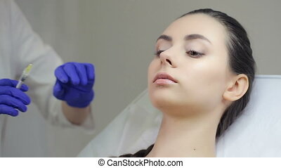 Doctor making injection in lips - Doctor making botox...