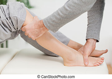 Doctor making joint mobilisation with the knee of a patient