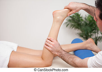 Doctor manipulating the leg of his patient