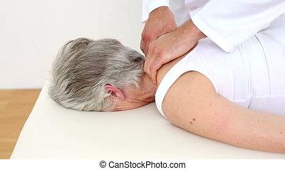 Doctor massaging senior patients shoulders at the...