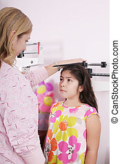 Doctor measure little child girl height growth