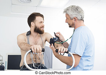 Doctor Measuring Blood Pressure Of Patient Cycling In Hospital