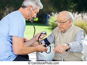 Male doctor measuring blood pressure of senior man at nursing home