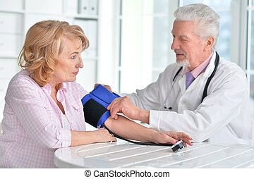 Doctor measuring blood pressure of woman