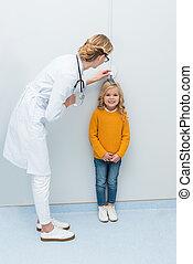 doctor measuring height of little girl