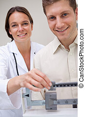 Doctor measuring patients weight - Doctor measuring her...