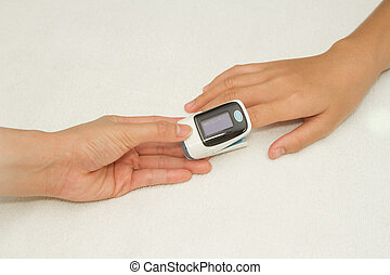Doctor measuring pulse rate and oxygen levels with Pulse ...