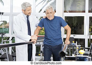 Doctor Motivating Senior Man To Walk In Fitness Studio