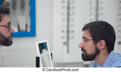 doctor ophthalmologist is helping a client to choose the...