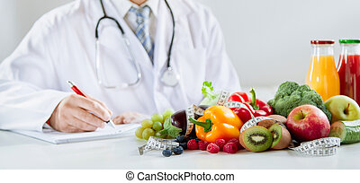 Doctor or dietitian writing a healthy food recipe with assorted fresh fruit and vegetables in the foreground with smoothies