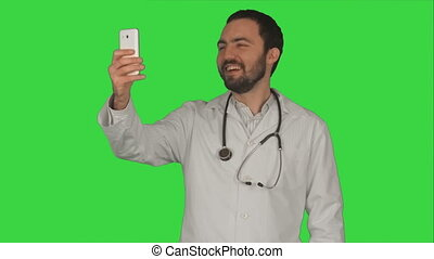 Doctor or medic taking a selfie with front camera of smartphone on a Green Screen, Chroma Key