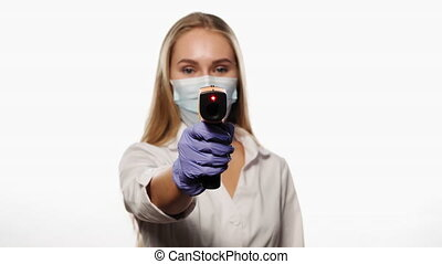 Doctor or nurse pointing sensor thermometer on camera wearing protective mask white medical hospital robe. Young blond haired nurse checking on patients or coworker temperature. 4k UHD.