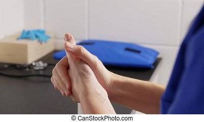 hygiene, healthcare and safety concept - doctor or nurse spraying antibacterial hand sanitizer at hospital
