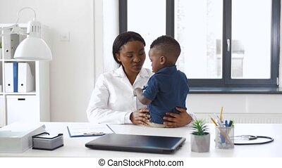 doctor or pediatrician with baby patient at clinic -...