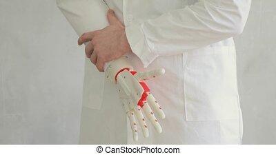 Doctor orthopedist is testing robotic prosthetic hand trying...