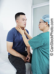 Doctor palpating neck of man