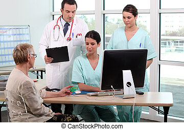 Doctor, patient, and medical secretaries at reception